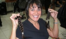 Woman holding braided pigtails that are chopped off