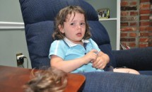 Little girl crying, lock of hair on table and very short bangs