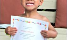 Little Boy holding a certificate