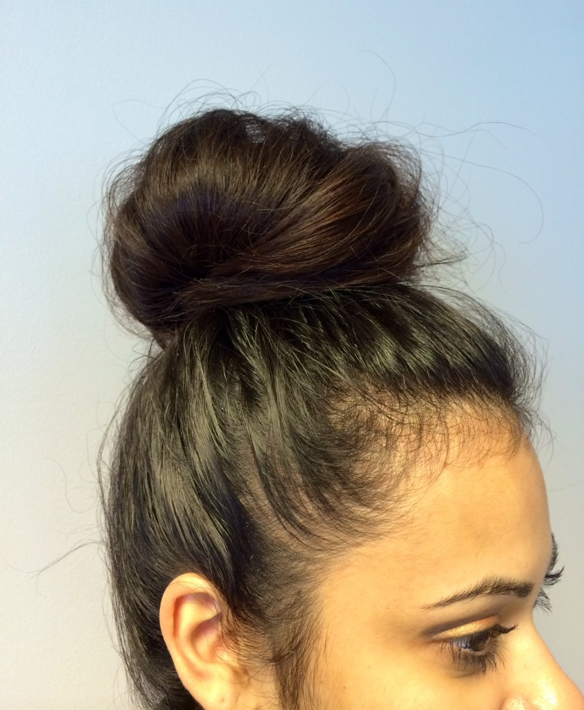 Young woman with top knot dark hair color