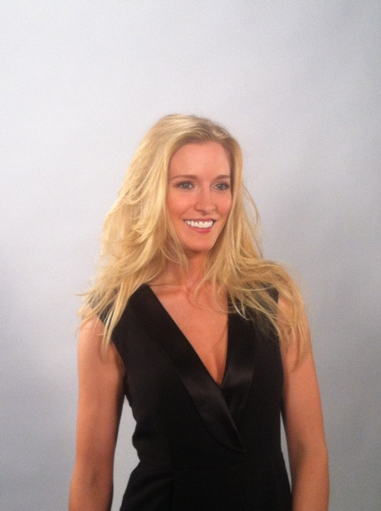 woman in black vest with long blonde blown out hair