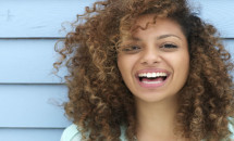 Young black woman with natural curly hair laughing