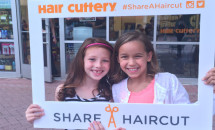 two young girls holding a share a haircut frame