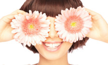 woman with short hair and bangs holding up gerber daisies over her eyes