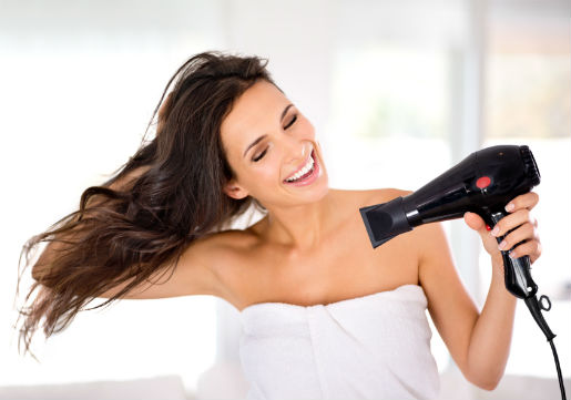 Woman blowdrying her long brown hair