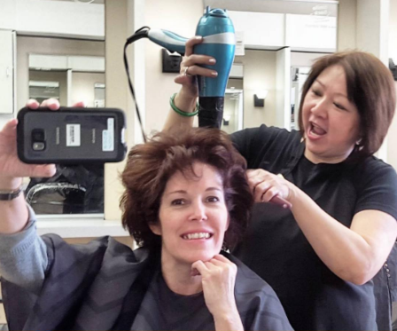 stylist blow drying a customers hair