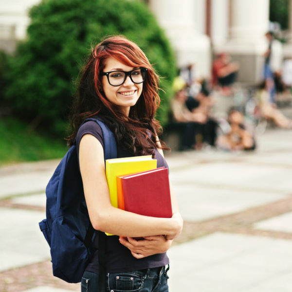 Young woman with backpack and books with two toned brown red hair