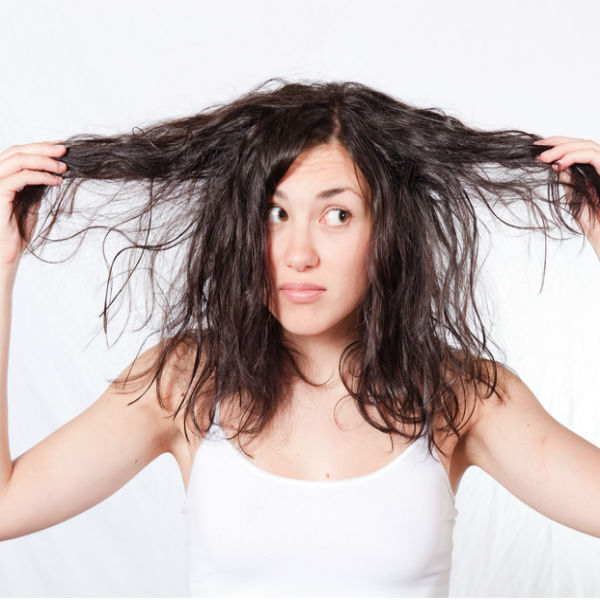 Woman holding out both sides of her unruly hair