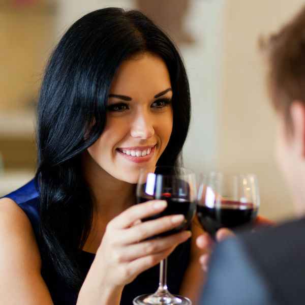 Dark hair woman having dinner with wine