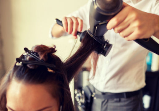 Stylist blowdrying hair