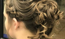 woman with braid and low ponytail with curls.