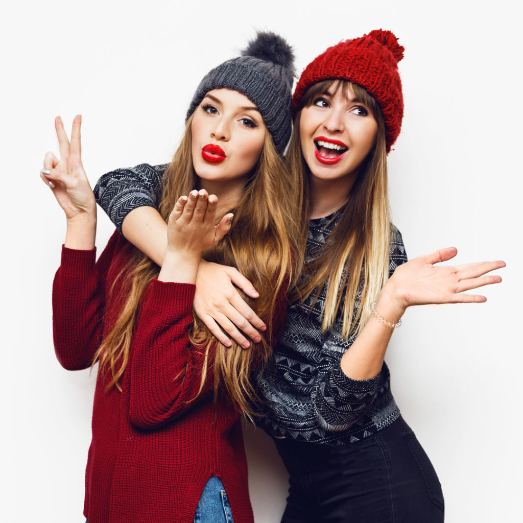 Two young women with winter clothing and long blonde hair