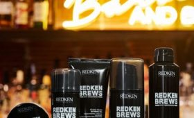 Redken Brews haircare and styling products on bar with neon light in background