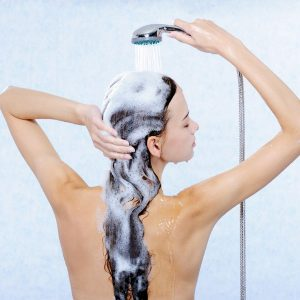 Color-treated hair tips woman washing long hair in shower