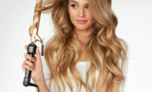 Woman with long hair making beach waves with curling iron